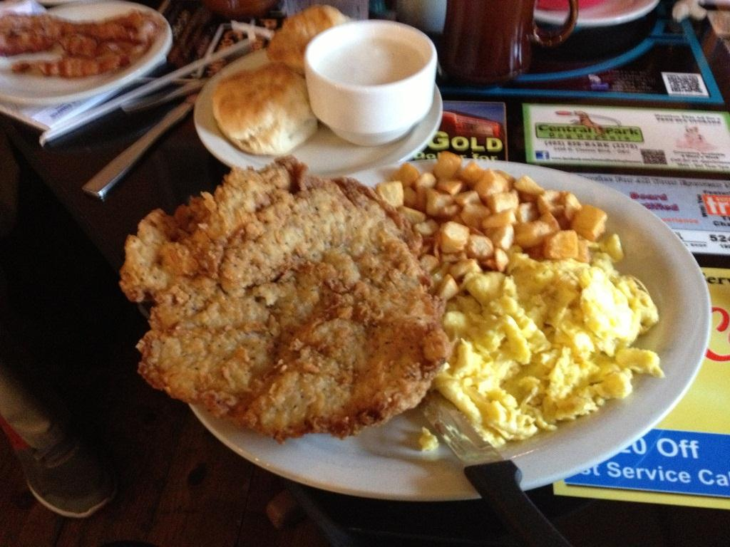 The Fry and Eggs on the Classen Grill menu comes with a large, hand-battered chicken fried steak, eggs your way, breakfast potatoes, and two biscuits with gravy.
