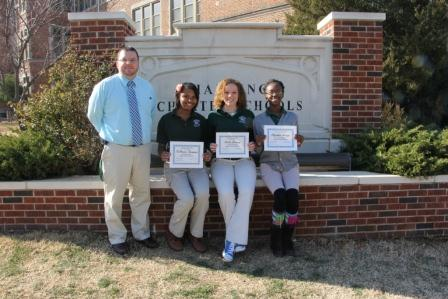 Principal Justin Hunt, left, stands with TeShauna Thompson, Saibra Journey and Elizabeth Shokoya in front of the school. Thompson, Journey and Shokoya were voted by their teachers as Awesome Eagles of the Month. Julius Stanfield was also named an Awesome Eagle (not pictured).