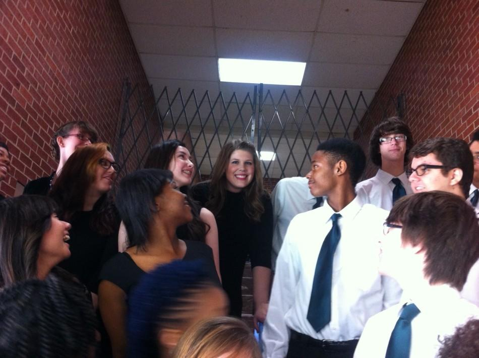 Vocal Music director Laura Gilson stands with her students in a stairwell at Western Heights High School in late February. This is the first time the choir advanced to the state choir competition.