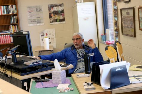 David Walsh sits behind his desk while educating his students during distance learning.